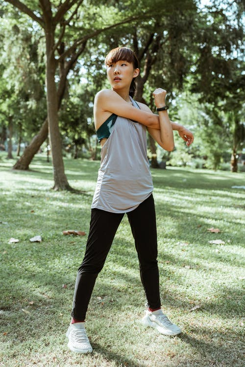 Asian sportswoman stretching arms before training in park