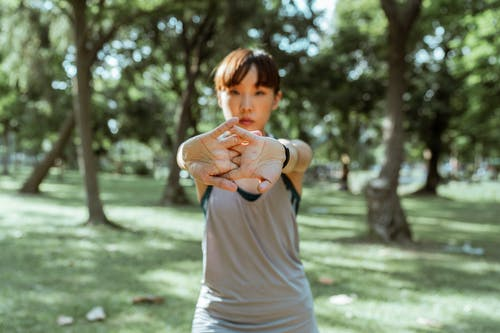 Focused adult Asian female athlete in sportswear standing alone in park and stretching hamstrings before workout