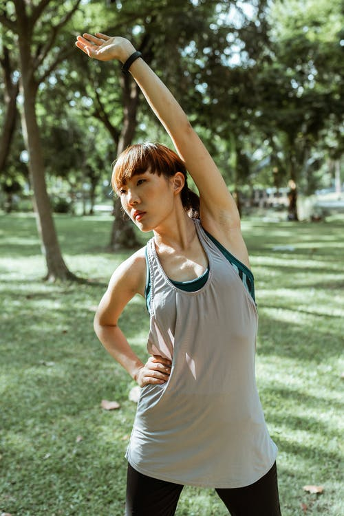 Serious Asian sportswoman stretching muscles in park