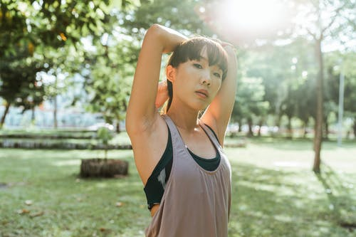 Young sportswoman in activewear stretching arms in park