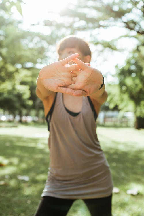 Fit sportswoman stretching arms in nature