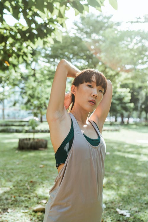 Calm young Asian female in back lit wearing sportswear stretching arms during fitness workout in sunlight in nature