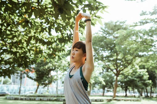 Positive calm Asian lady in sportswear doing arms stretching exercises while warming up in sunny summer park