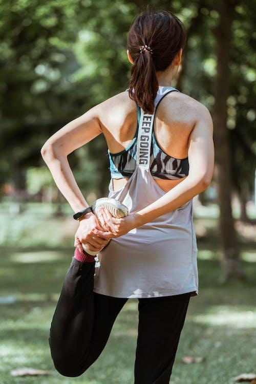 Fit sportswoman stretching legs in park