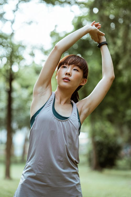 Focused young sportswoman stretching arms in nature
