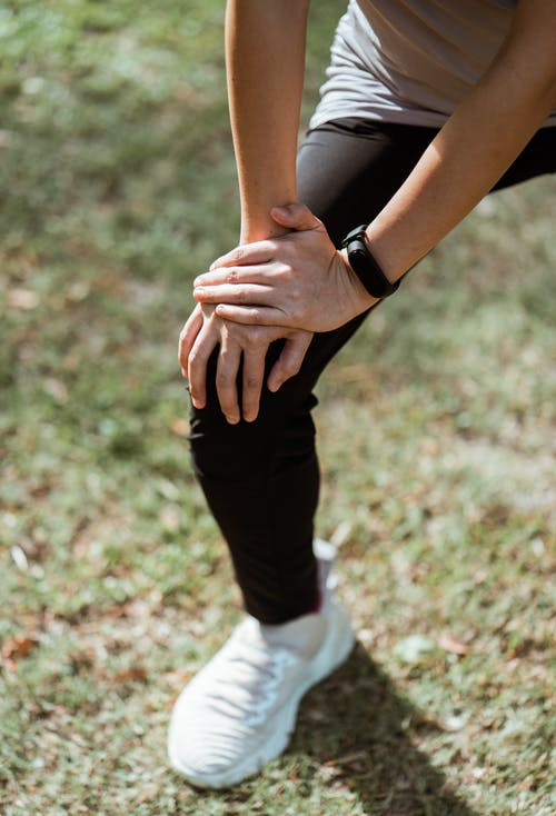 Crop anonymous slim sportswoman in black leggings and white sneakers stretching legs before jogging while warming up on green meadow in sunlight