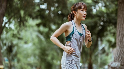 Positive calm sportswoman jogging in nature
