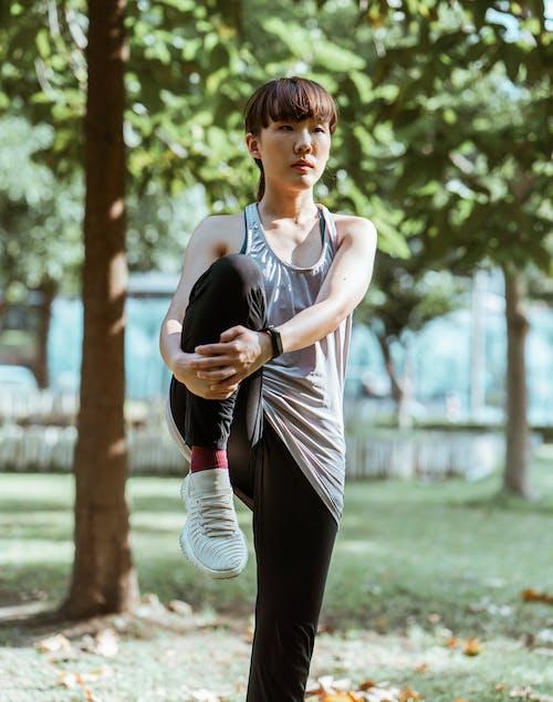 Determined sportswoman stretching legs in summer park