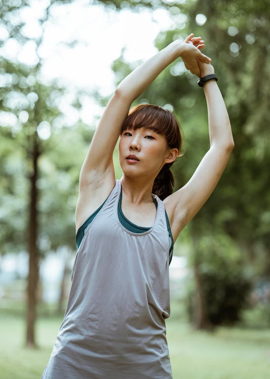 Determined young Asian sportswoman in gray sports top raising arms and doing stretching exercise while training in green sunny forest and looking at camera thoughtfully