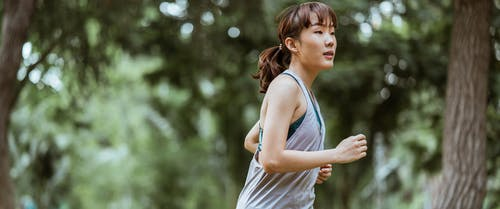 Positive Asian sportswoman jogging in countryside