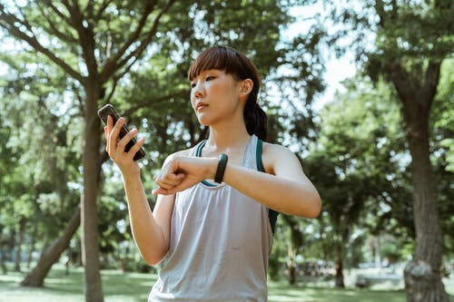 Content sportswoman using smartphone and fitness tracker