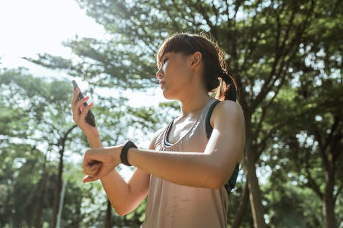 Sporty sportswoman with smartphone and fitness bracelet in park