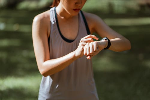Crop fit sportswoman checking fitness tracker in nature