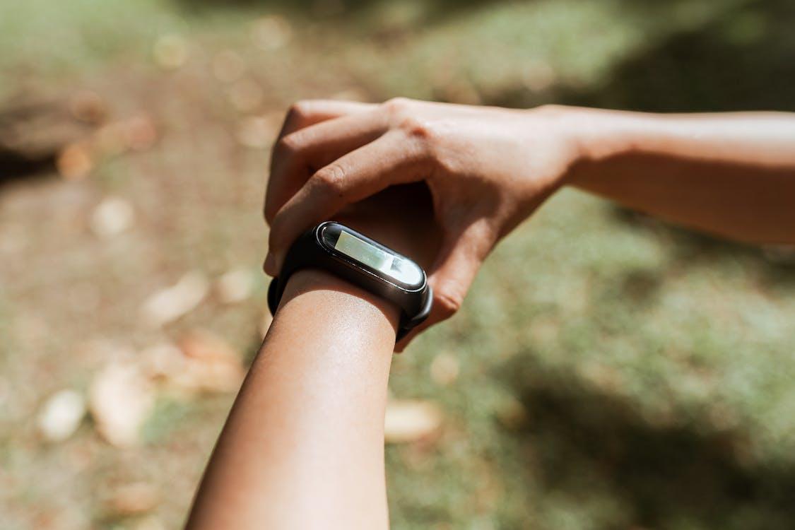 Crop sportswoman checking fitness bracelet against green lawn