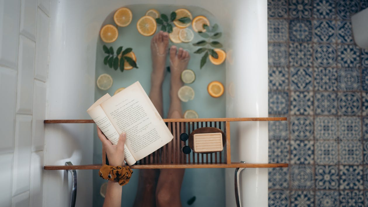 lady taking a bath and reading a book, engaging in self-care