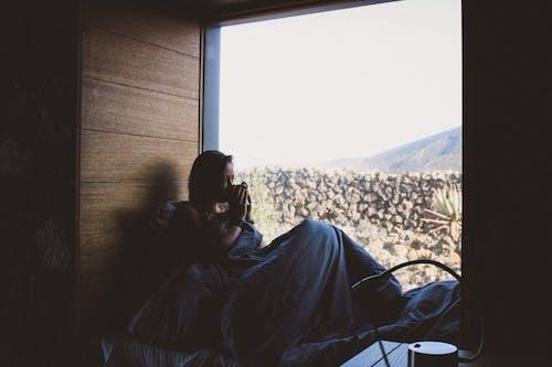 Man in Black Jacket Sitting on Bed