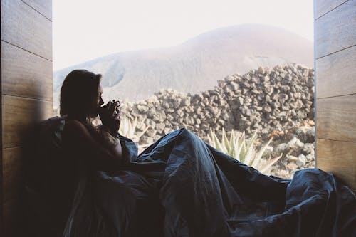 Woman in Black Dress Sitting on White Flower Field