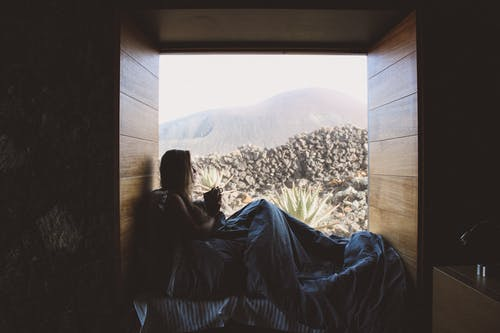 Woman Lying on Bed of Snow Covered Mountain