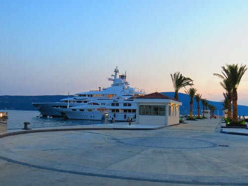 Scenery of contemporary white yachts moored on paved embankment with tropical palms against peaceful hills in evening