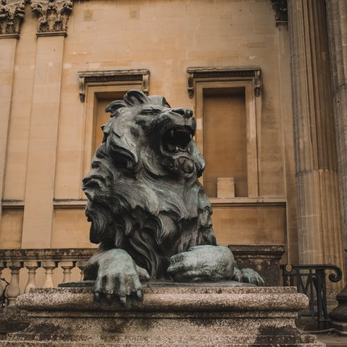 Statue of roaring lion outside old building