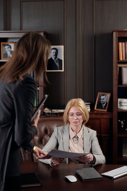 Woman in Black Blazer Sitting Beside Woman in Gray Blazer