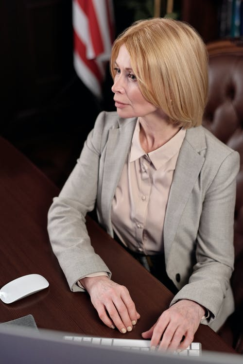 Woman in Gray Blazer Sitting by the Table