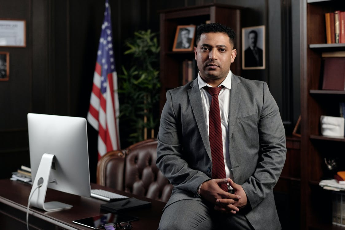 Businessman Sitting on his Desk and Looking at the Camera