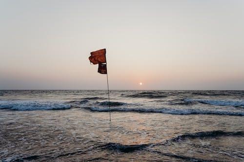 Orange and White Flag on Pole on Sea
