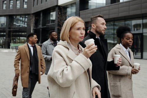 Woman in Beige Coat Holding Black and White Ceramic Mug