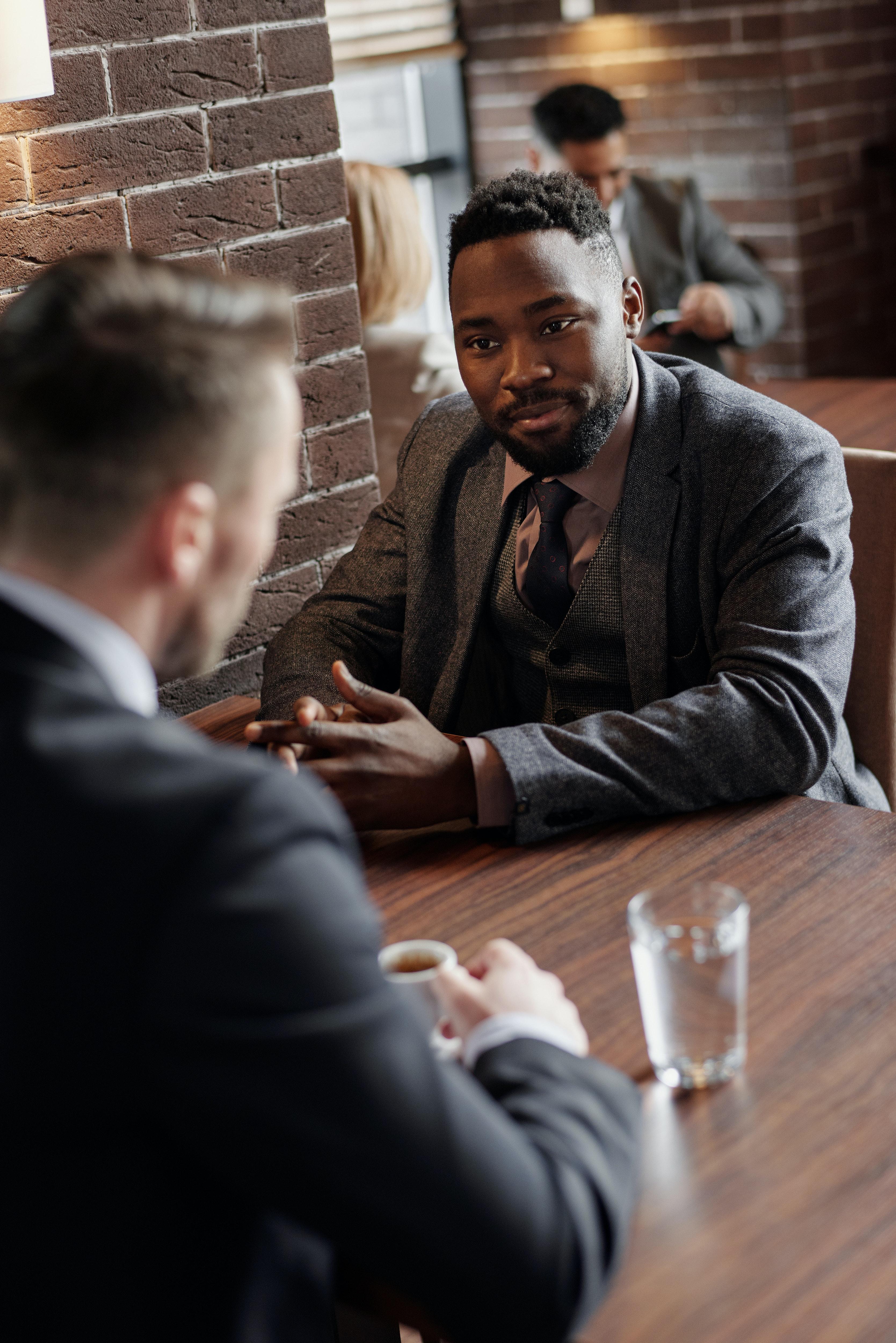Two men having a meeting at a restaurant. | Photo: Pexels