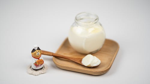 Jar with delicious plain yogurt and wooden spoon on saucer