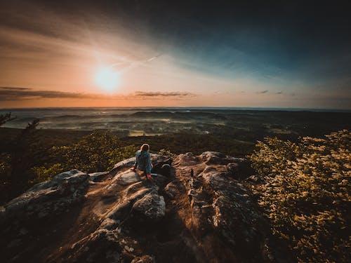 Traveler on rocky hill admiring sunset over sea