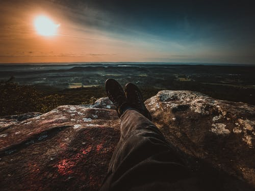 Crop faceless person lying on rocky hilltop with legs crossed and admiring waving sea in evening