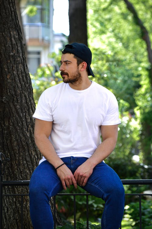 Man in White Crew Neck T-shirt and Blue Denim Jeans Sitting on Black Metal Bench