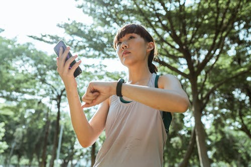 Young ethnic woman connecting smartphone and smart watch