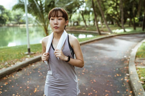 Confident woman with towel running in park