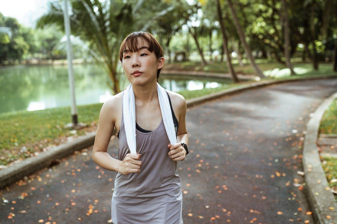 Slim ethnic woman wearing sportswear running in park