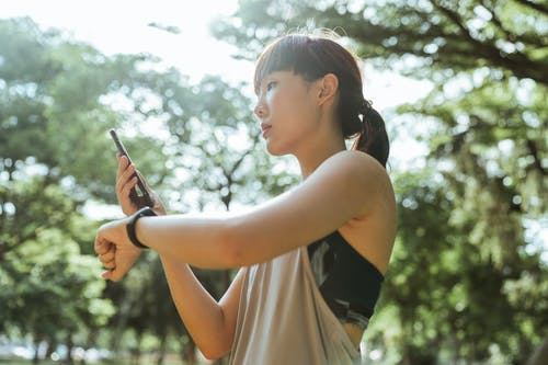 Young Asian woman using devices for fitness in park