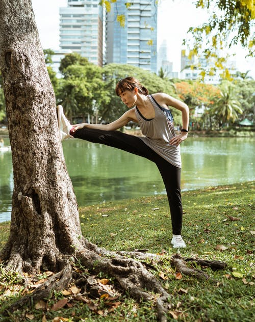 Full body of ethnic sportive woman in sportswear stretching near tree close to park pond