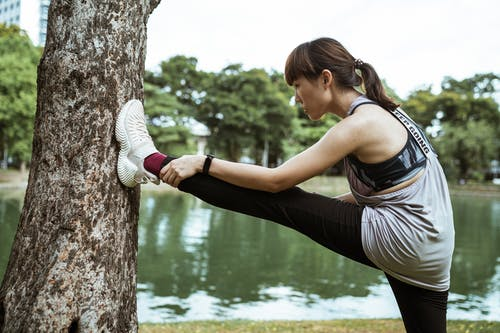 Young Asian woman warming up near pond