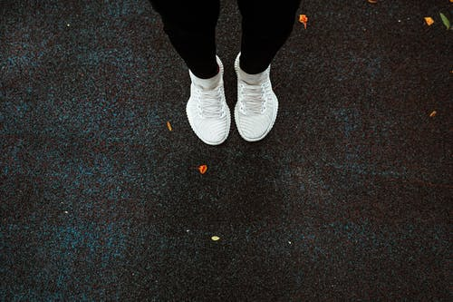 Anonymous person in white sneakers jumping on rubber ground