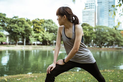 Pensive sportive woman exercising near pond