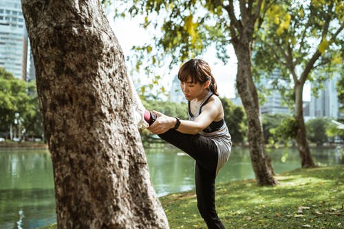Young Asian woman leaning on tree while stretching