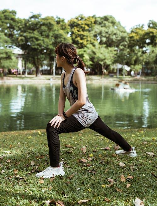 Slim Asian woman exercising on pond shore