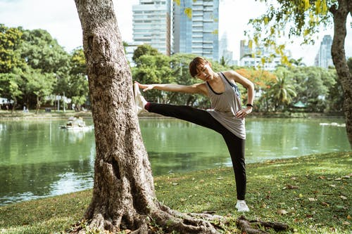 Full body ethnic flexible female in sportswear looking down while warming up near pond in park