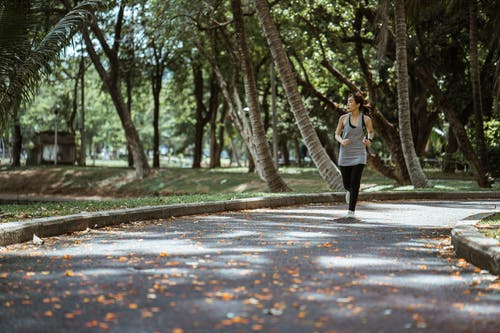 Asian woman jogging in park in sunny day
