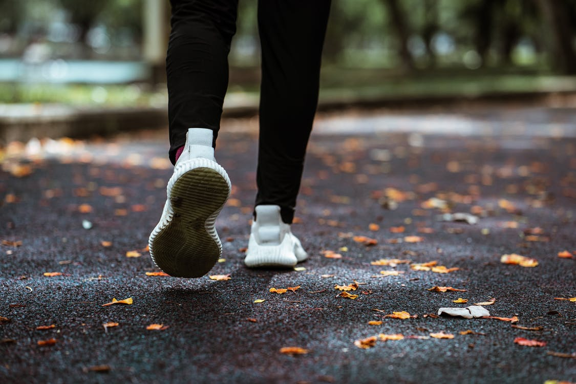 Legs of anonymous person in white sneakers and black leggings running on sidewalk