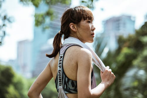 Side view of ethnic female in activewear with towel over neck looking away while resting after gymnastic in sunny day
