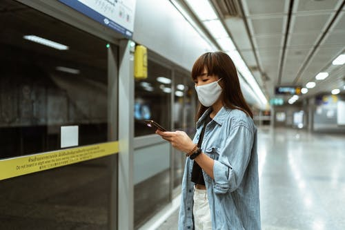 Woman Wearing a Face Mask and Holding a Smartphone