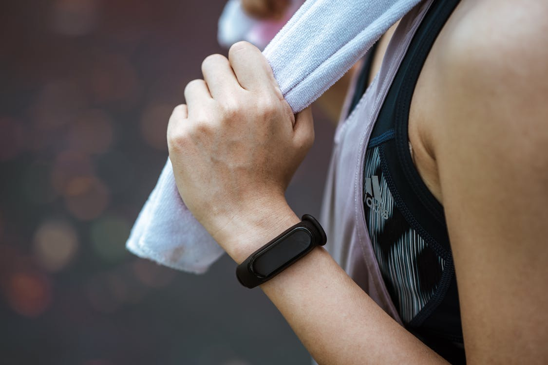 Crop unrecognizable sportswoman in smart watch using towel after workout
